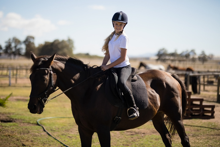 Portrait of smiling girl riding a horse in the ranch