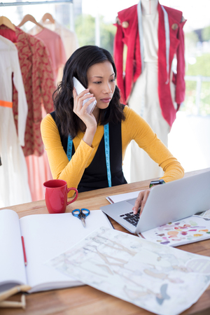 Female designer using laptop while talking on mobile phone in office Stock Photo
