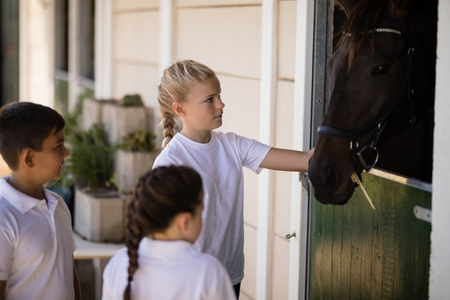 Three kids looking at the brown horse in the stable Stock Photo - 82159987