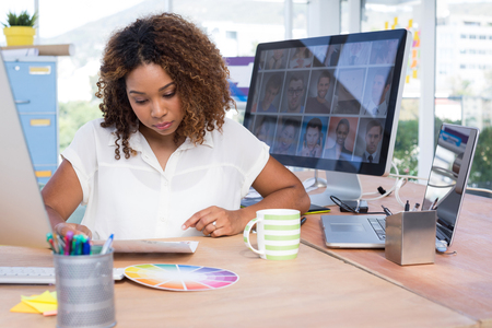 pen holder: Female graphic designer looking at photos in office Stock Photo