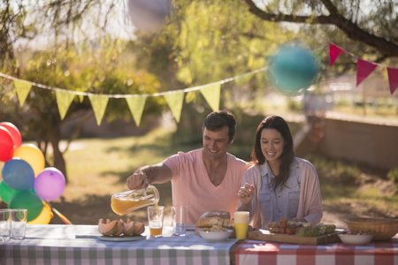 Happy couple having meal in park on a sunny day Stock Photo