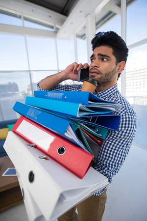 Male executive holding stack of files while talking on mobile phone in the office