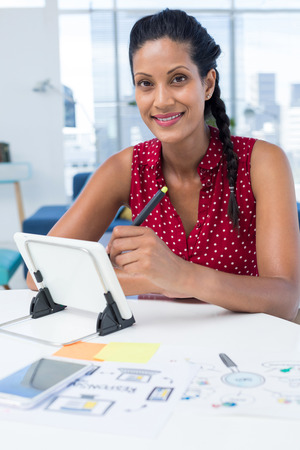Female graphic designer using graphic tablet at desk in the office
