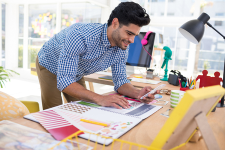Male graphic designer using mobile phone while working at desk in the office Stock Photo