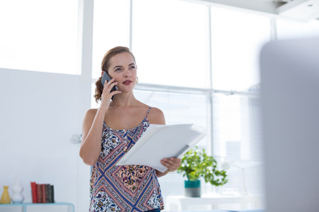 Female executive talking on mobile phone while holding document in the office Stock Photo