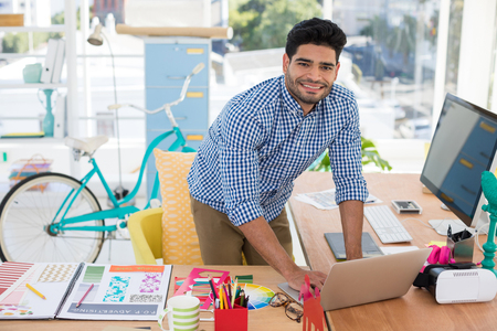 Graphic designer working on laptop at desk in the office