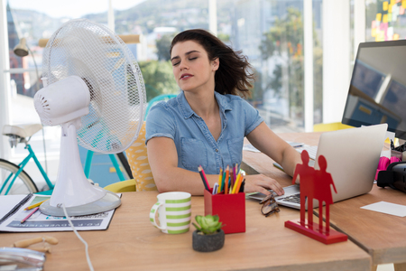 Female executive enjoying breeze from table fan in the office