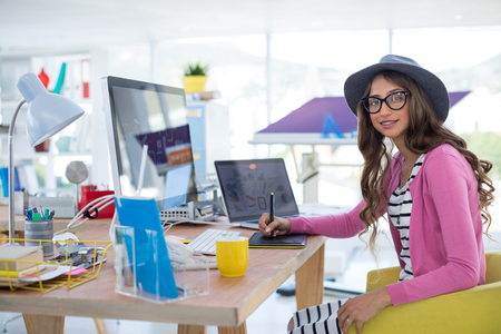 stylus: Female graphic designer using graphic tablet at desk in the office