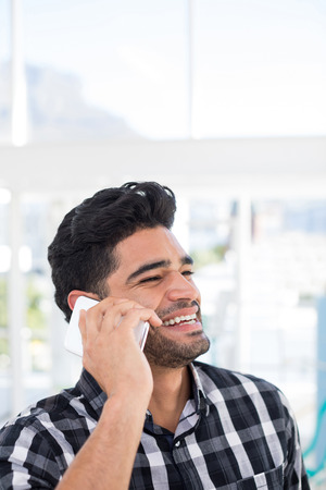 Male executive talking on mobile phone in the office