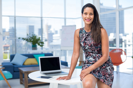 Portrait of female executive sitting on desk in the office