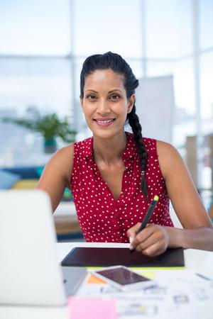 Female graphic designer using digital tablet at desk in the office