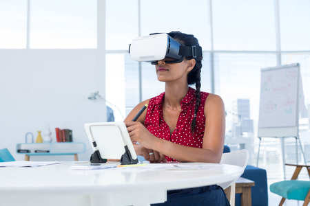 Female graphic designer in virtual reality headset using digital tablet at desk in the office