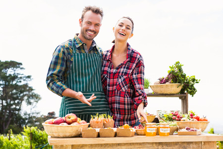 looking for work: Portrait of happy young couple selling organic vegetables at farm