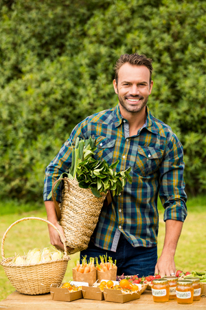 looking for work: Portrait of smiling handsome man selling organic vegetables while standing at farm Stock Photo