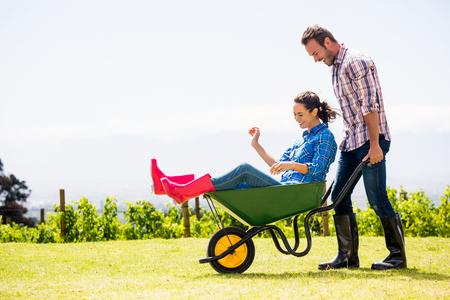 Dronken de vrouwenzitting van de jonge man in kruiwagen bij gazon op zonnige dag