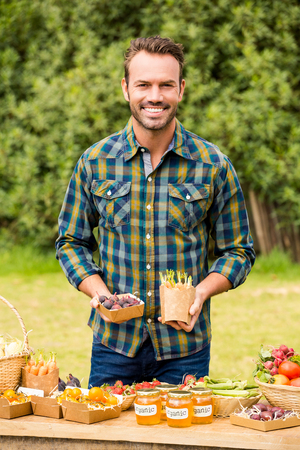 looking for job: Portrait of smiling young man selling organic vegetables at farm