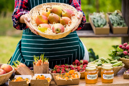 large group of business people: Midsection of woman selling pears while standing at farm Stock Photo