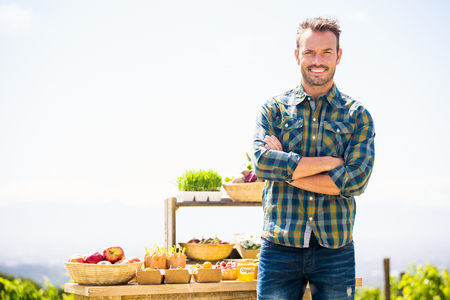 looking for job: Portrait of smiling young man with arms crossed standing at farm
