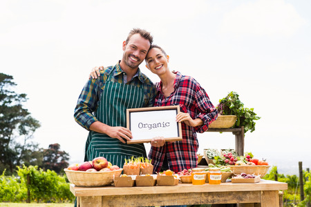 Portrait of smiling couple with blank blackboard selling vegetables at farm