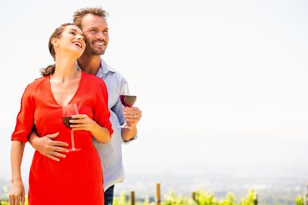 赤ワインのブドウ畑を離れて見てロマンチックなカップルは笑みを浮かべてください。