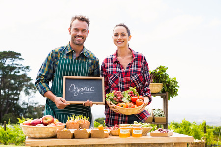 looking for job: Portrait of couple with blackboard and basket selling organic vegetables at farm