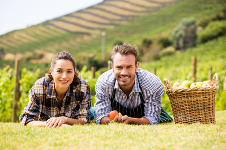 Portrait of smiling young couple lying down at vineyard