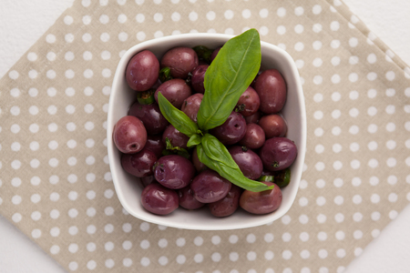 Overhead view of black olives with herb in bowl on napkin