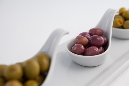 Cropped image of green and black olives in containers on tray against white background