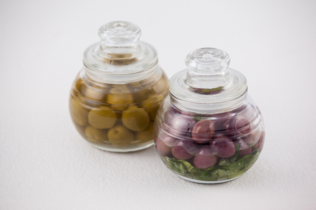 single word: High angle view red and green olives in glass jar on white table