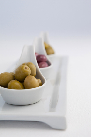Brown and green olives in containers against white background Stock Photo