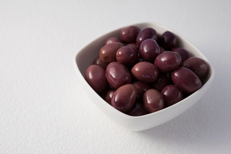single word: Close up of brown olives in container on white wooden table
