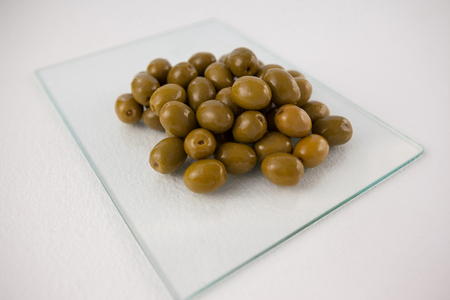 single word: Close up of green olives on glass slab at table Stock Photo