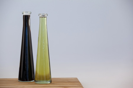 Black and green olive oil in bottle on table against wall