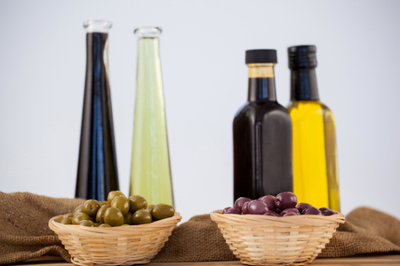 single word: Olives in wicker basket with oil bottle on table against wall Stock Photo