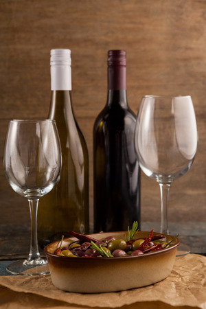 single word: Wine bottles by olives served in container on table against wall