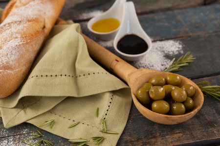 single word: Close up of olive oil by bread and napkin on table