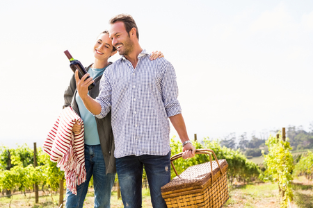 Smiling man with woman holding wine bottle and basket at vineyard Stock Photo
