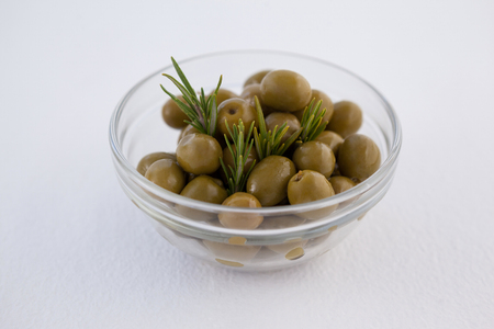 toothpick: Close up of green olives with herb in bowl on table