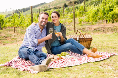 Full length portrait of young couple holding wineglasses at vineyard Stock Photo