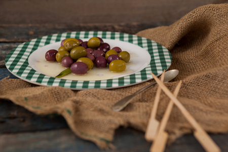 single word: Close up of green and black olives served in plate on wooden table Stock Photo