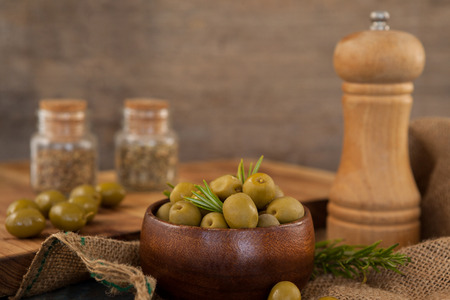 single word: Olives and rosemary in bowl by wooden pepper shaker on table Stock Photo