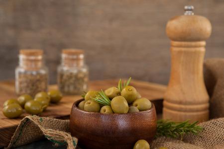 Olivy a rozmarýnu v misce dřevěnou pepřovou třepačkou na stole Reklamní fotografie