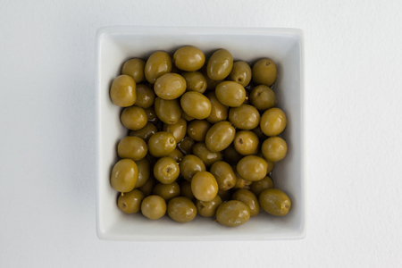 Overhead view of green olives in white container on table