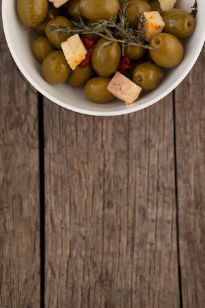 single word: Overhead view of olives with cheese served in bowl on wooden table