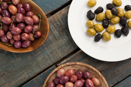 single word: Overhead view of olives in bowls and plate on wooden table