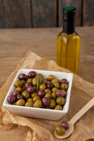 High angle view of olives with rosemary served in bowl by oil bottle on table