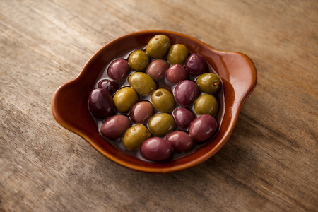 High angle view of olives with oil in wooden container on table
