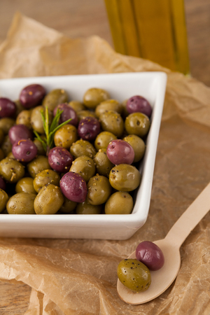 Close up of olives with rosemary served in bowl by spoon on paper at table
