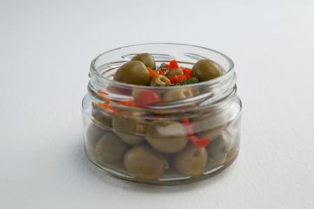 single word: Close up of green olives and herbs in glass jar on table Stock Photo
