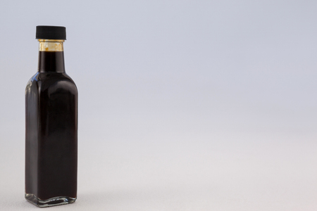 single word: Oil bottle with lid against wall Stock Photo